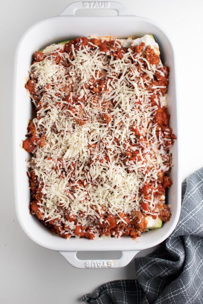 Shredded mozzarella cheese on zucchini boats.