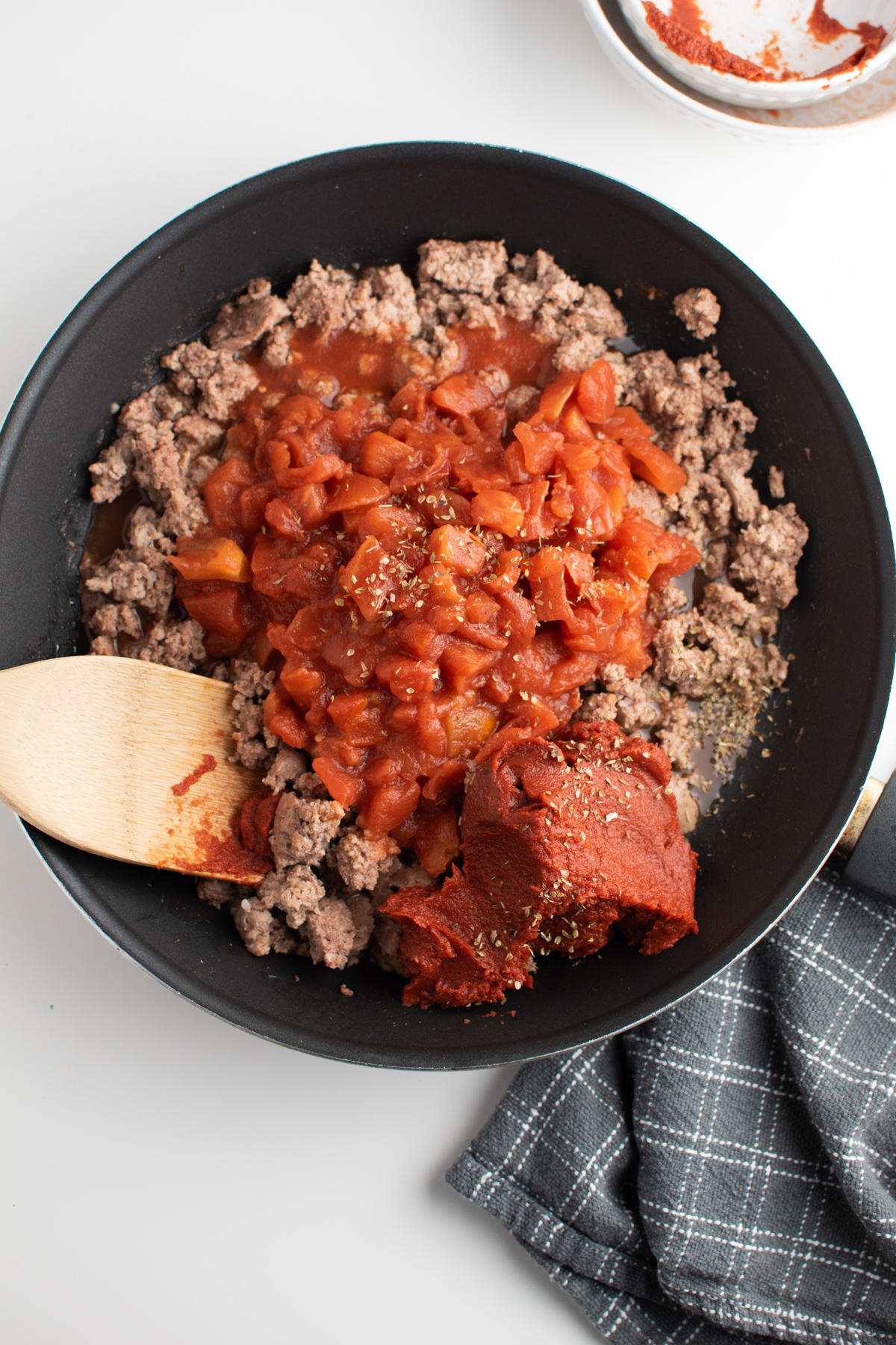 Tomatoes, tomato paste, spices and ground beef in large pan.