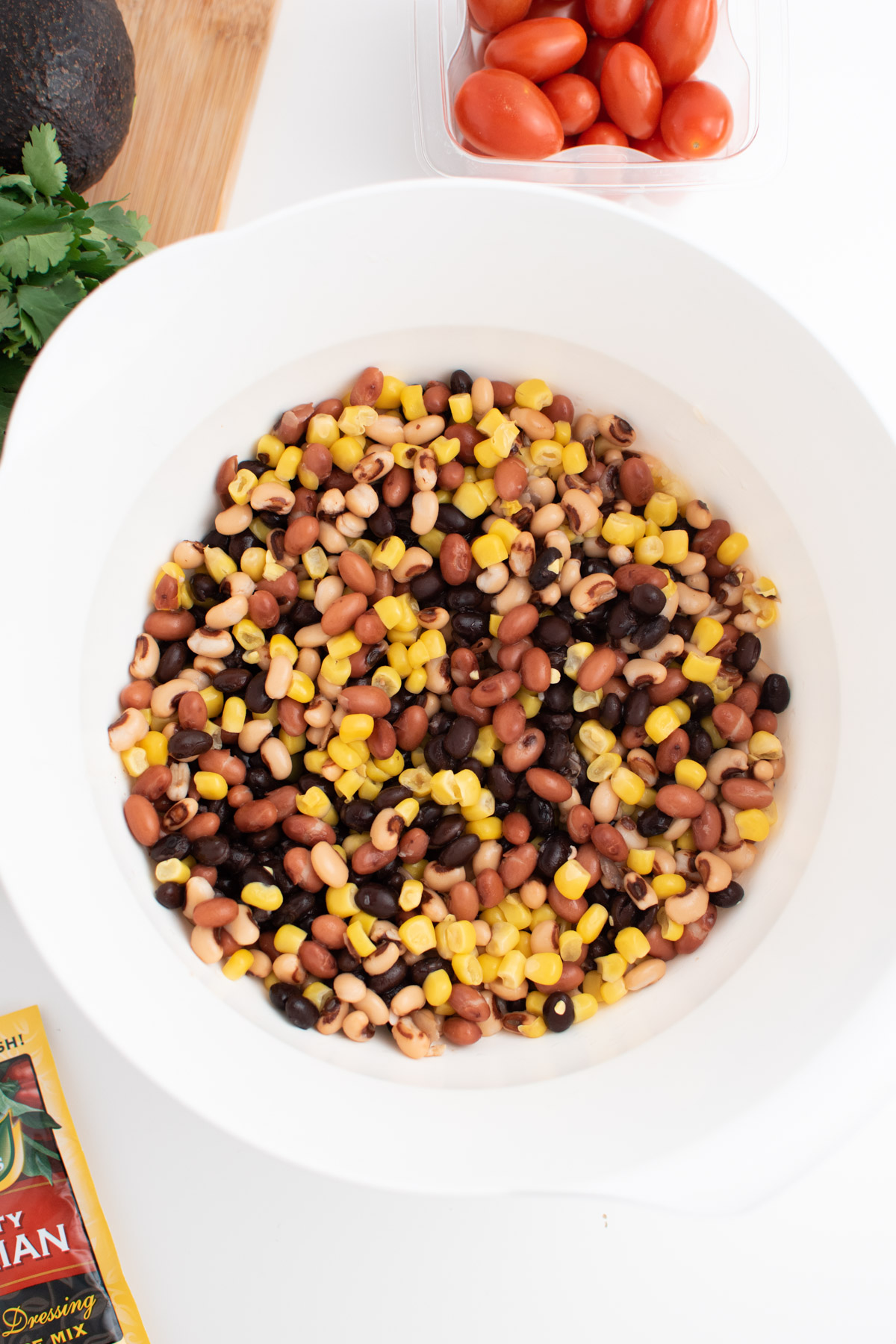 Rinsed beans and corn in large white mixing bowl to make cowboy party dip.