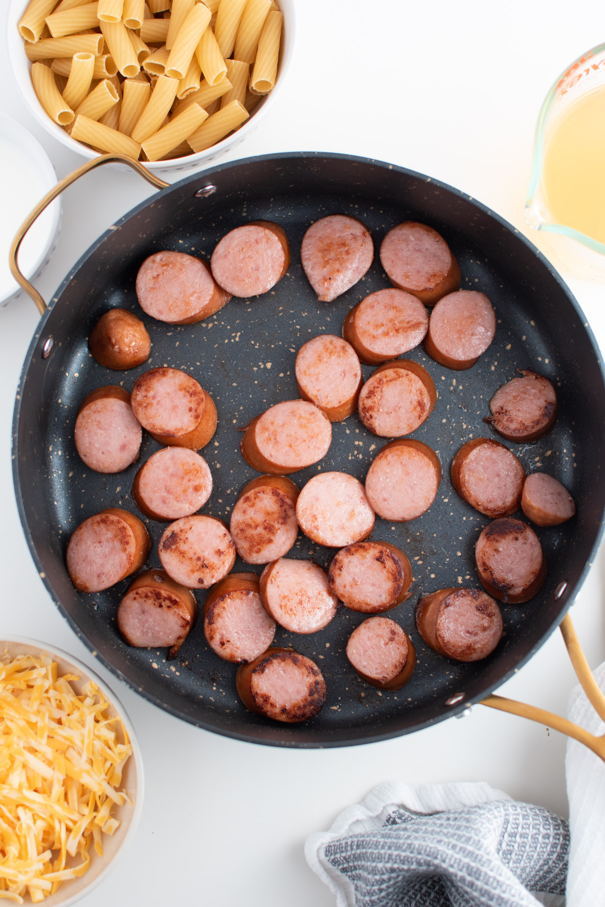 Browned kielbasa in black speckled skillet with bowls of cheese and uncooked noodles surrounding.