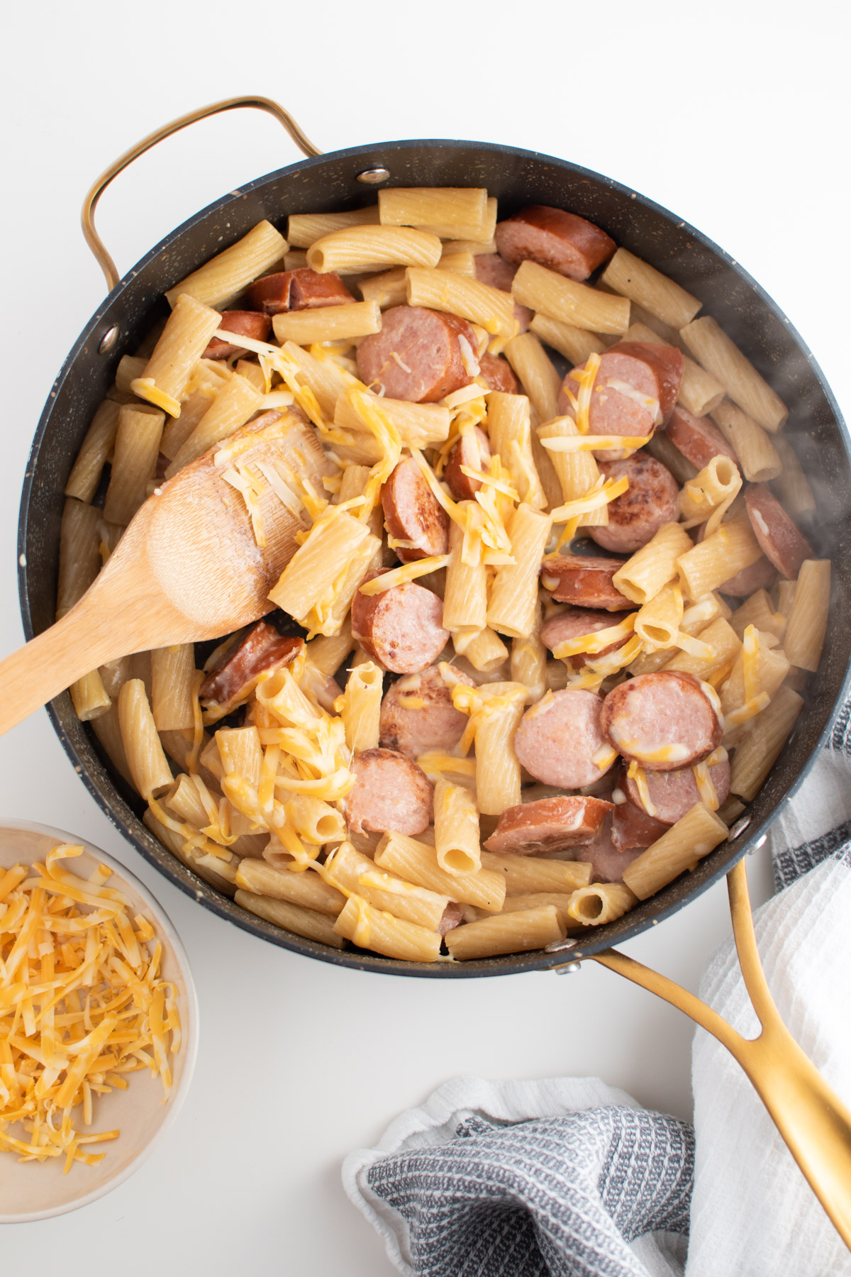 Shredded cheese on top of steamy kielbasa pasta in skillet with wooden spoon.