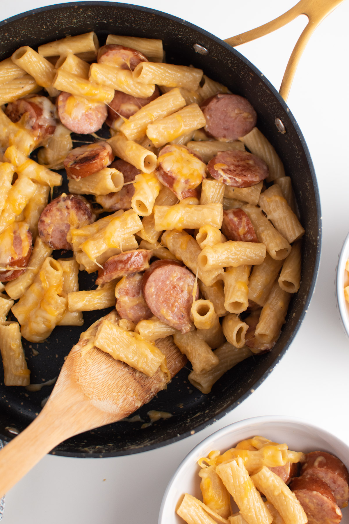 Cheesy kielbasa pasta in black skillet with wooden spoon and bowls of pasta surounding.