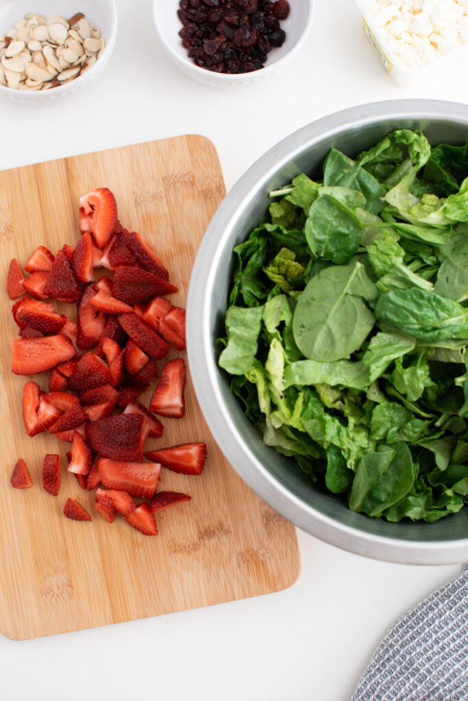Chopped strawberries, lettuce, and spinach.