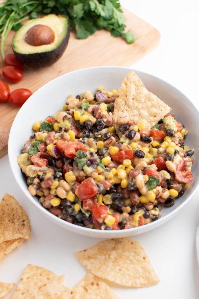 Bowl of cowboy caviar with tortilla chips next to cutting board with fresh veggies.