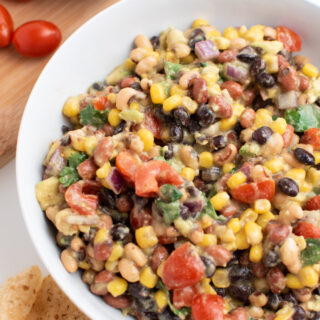 Cowboy caviar with avocado, black beans, onions and tomatoes in white bowl.