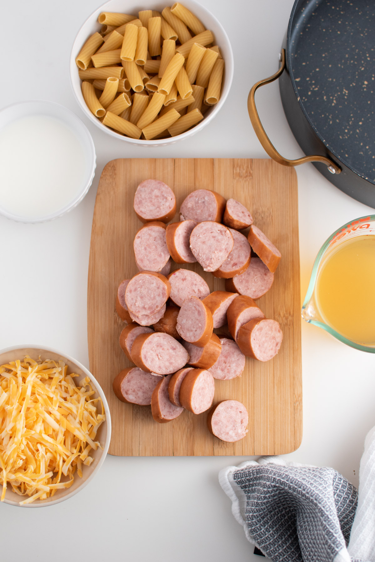 Kielbasa pasta ingredients including shredded cheese, milk, broth and sausage on white table.