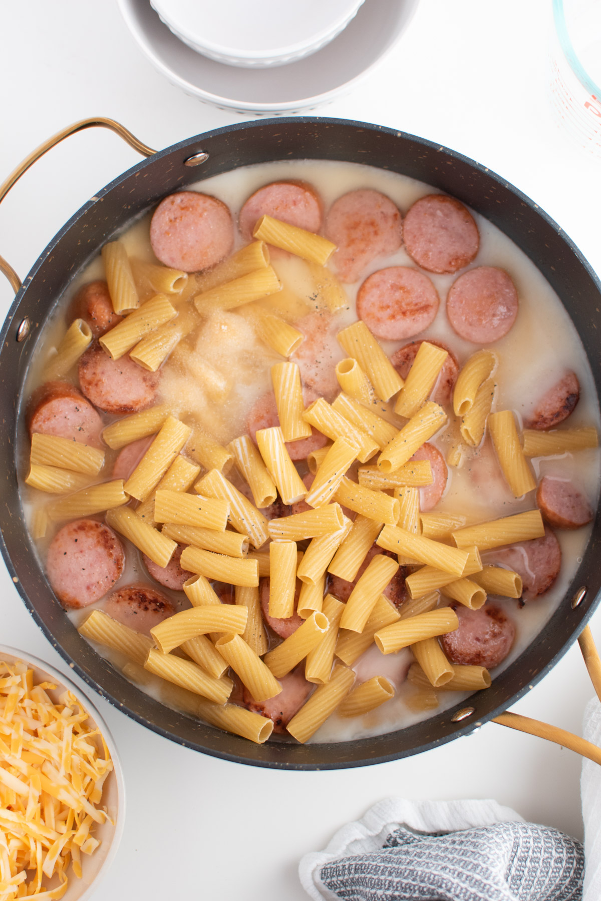 Uncooked rigatoni noodles, cooked kielbasa sausage, and broth in large black skillet.