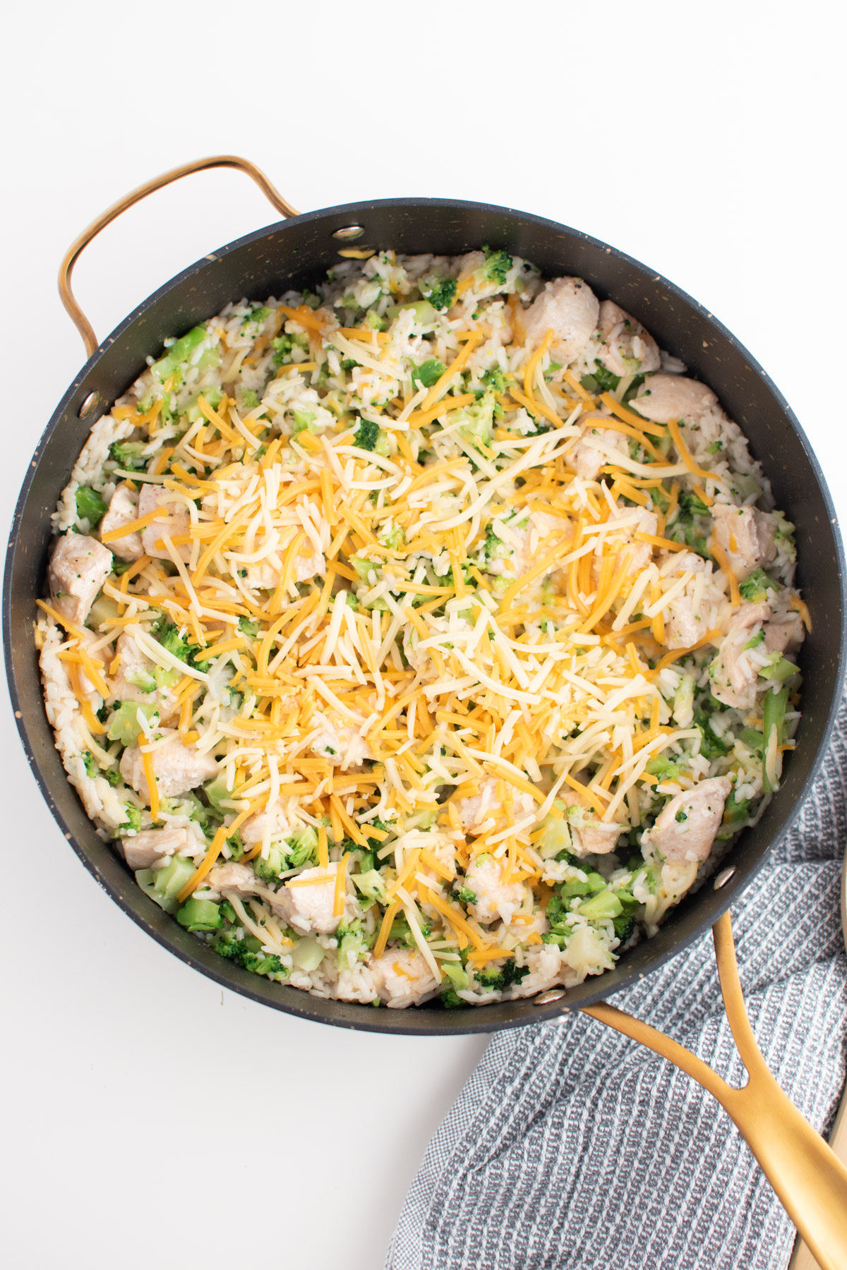 Shredded Colby jack cheese sprinkled over cooked chicken and broccoli in skillet.
