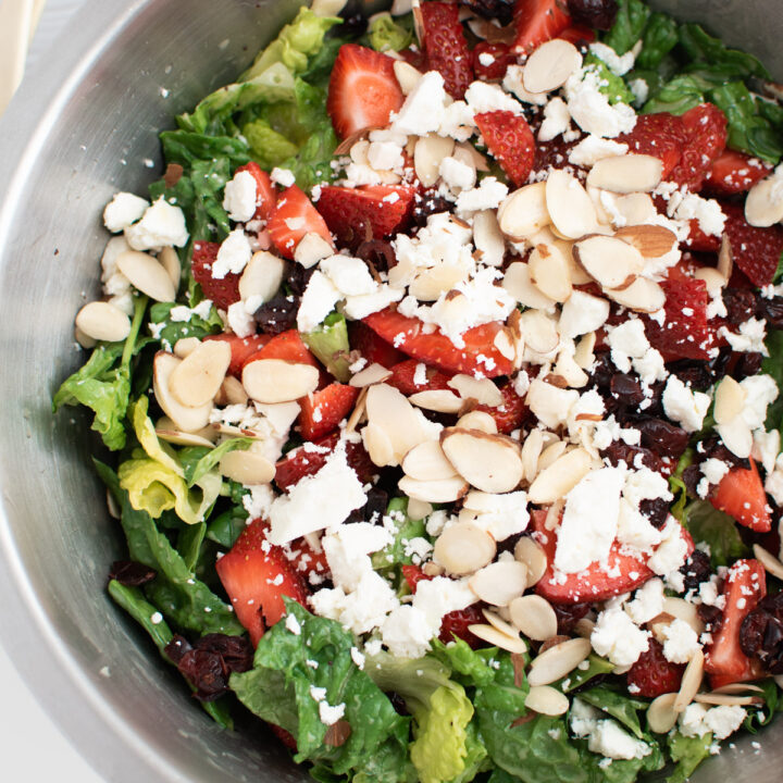 Large bowl of spinach strawberry almond salad.