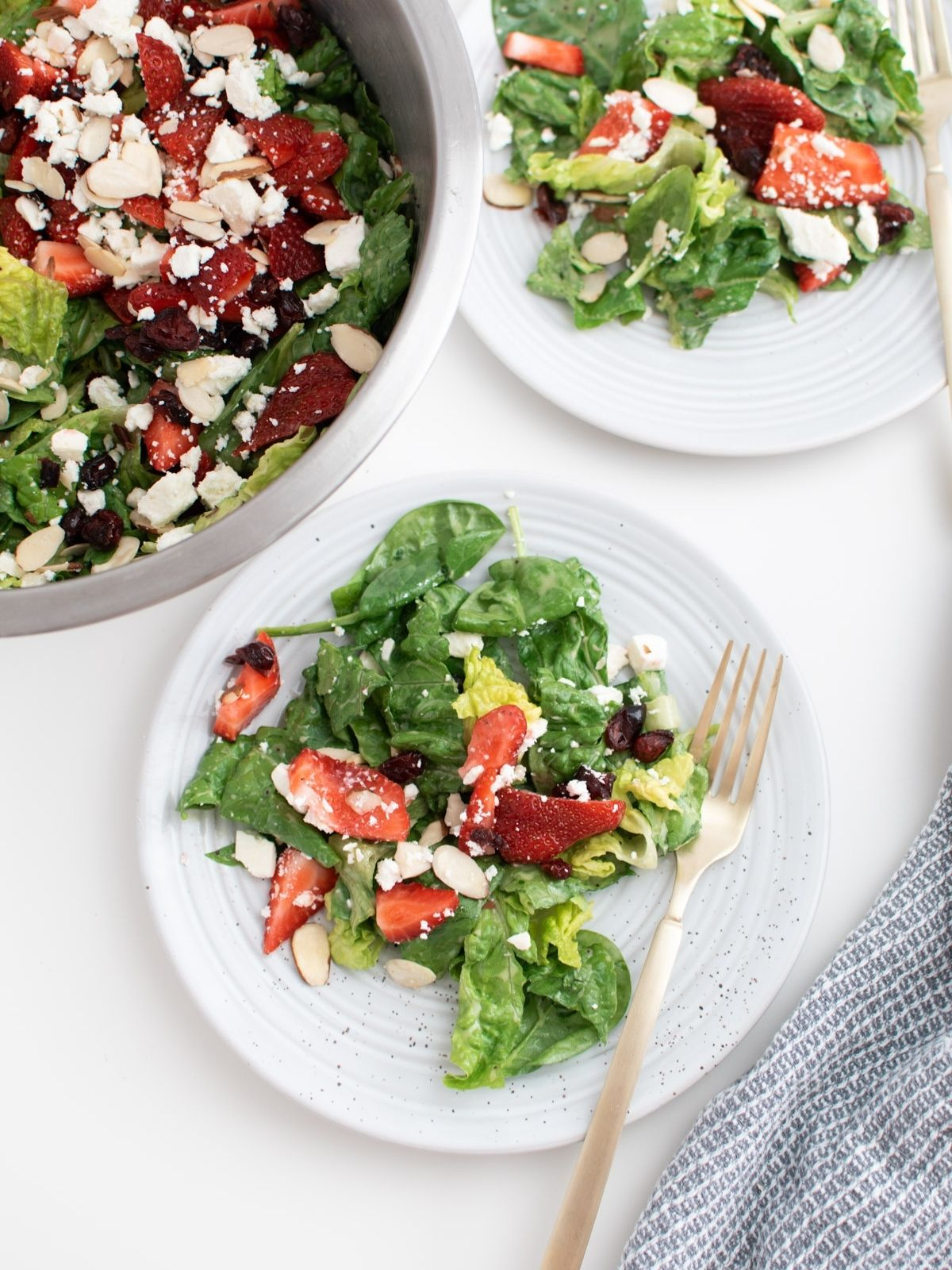 Two white plates of spinach strawberry salad with feta and almonds on white table.
