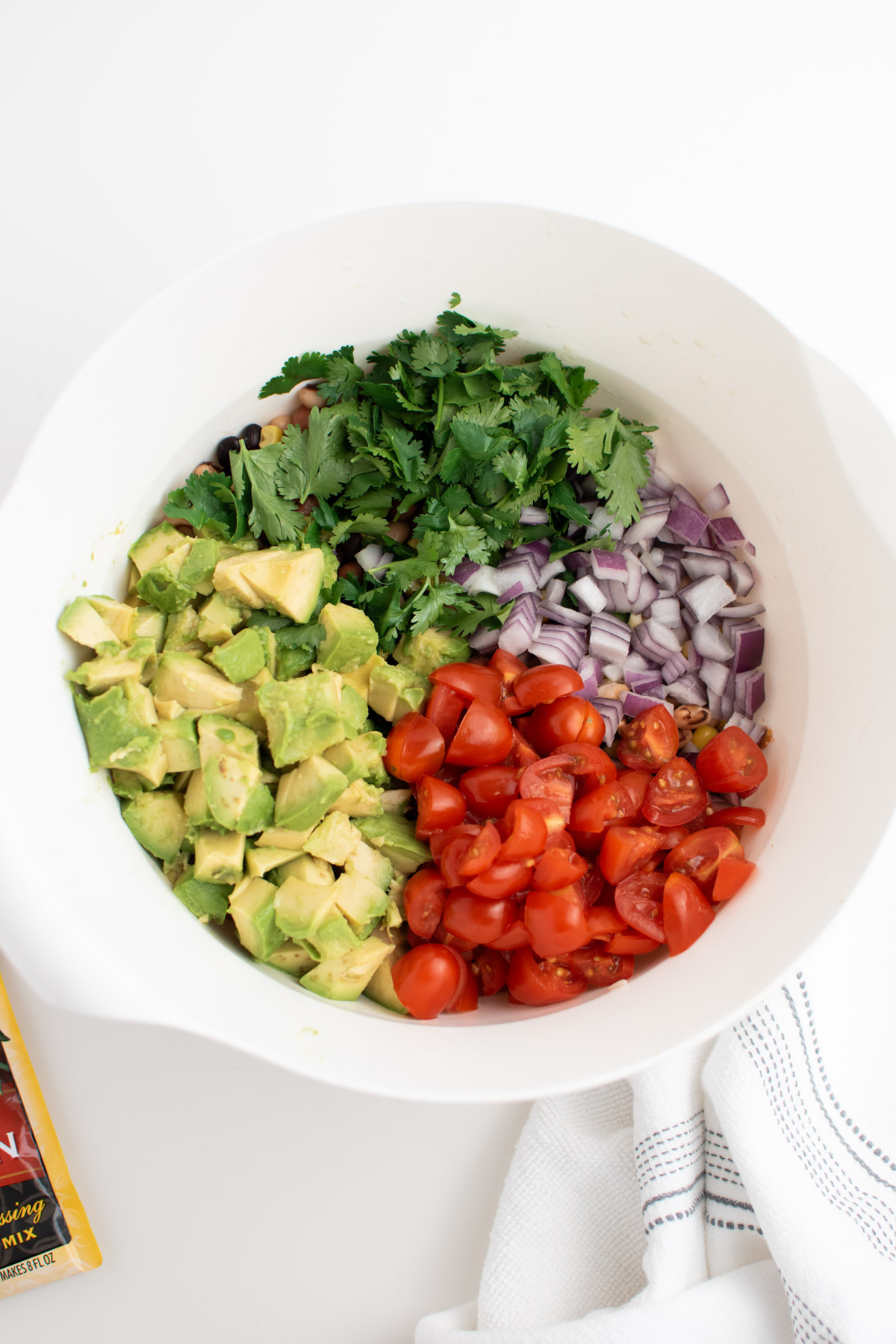 Chopped avocado, tomatoes, red onion and cilantro in a white mixing bowl.