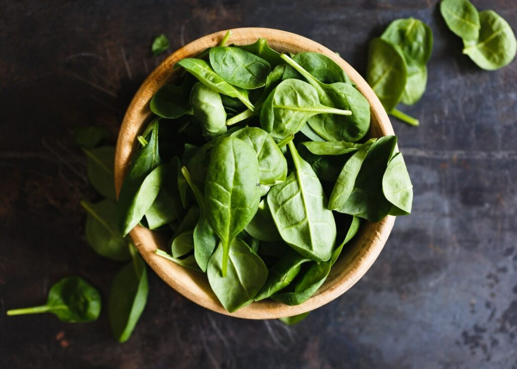 Basil leaves in wooden bowl and scattered on dark metal table.