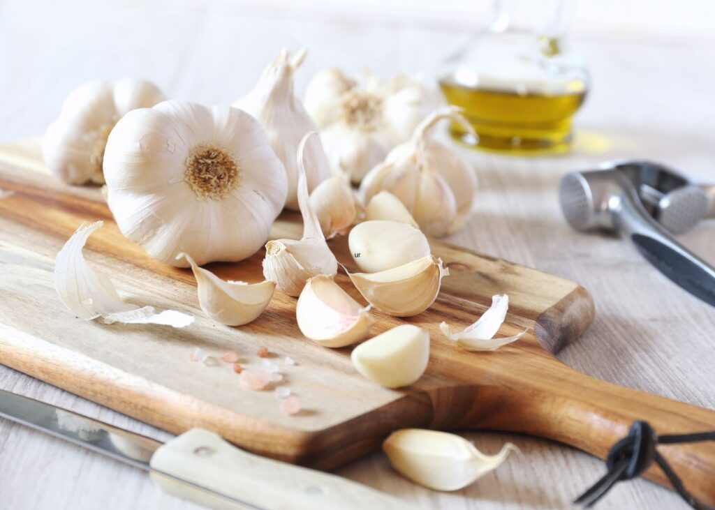 Garlic bulbs and cloves on wooden cutting board next to a knife with garlic press and oil in background.