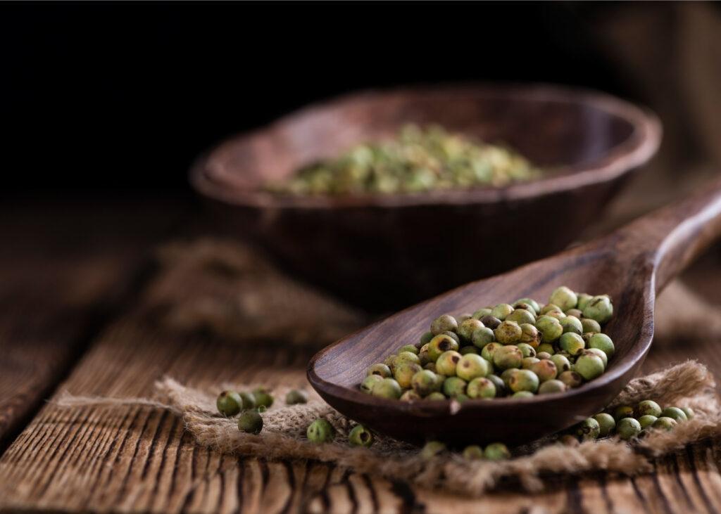 Green peppercorns in wood bowl.