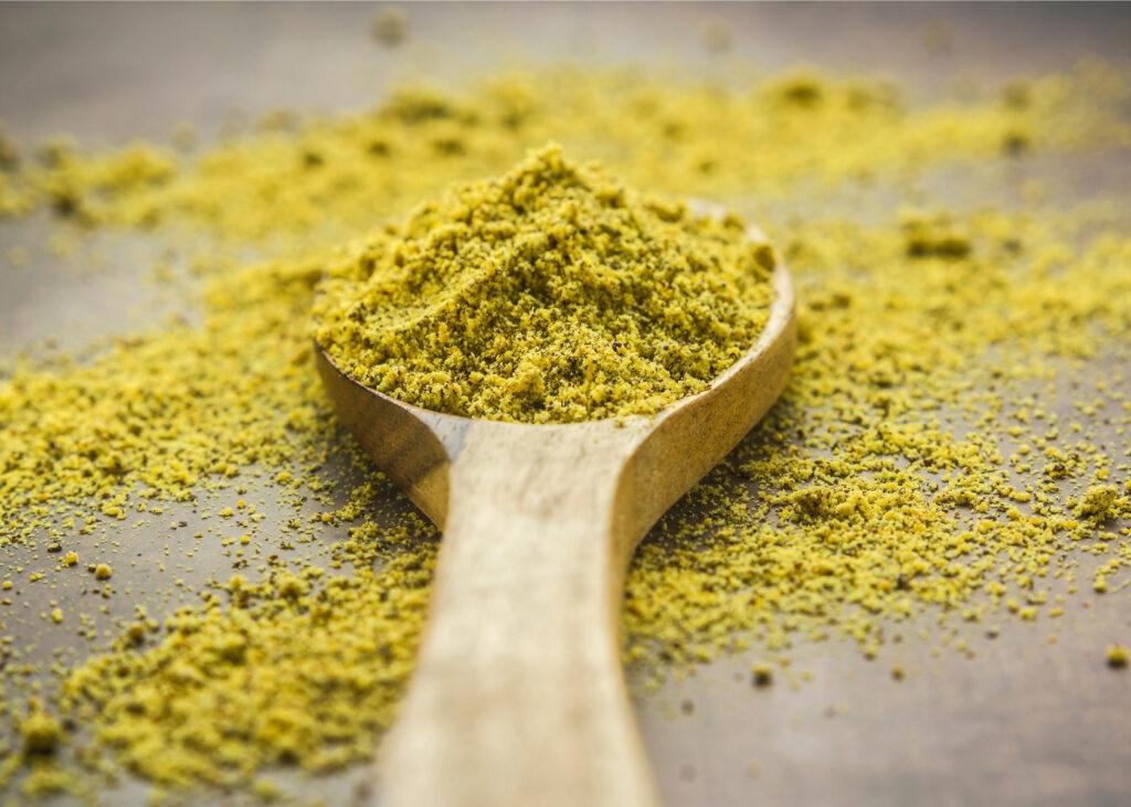 Ground mustard on wooden spoon.