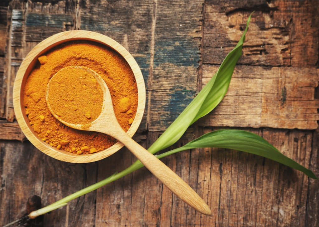 Ground turmeric in wooden bowl.