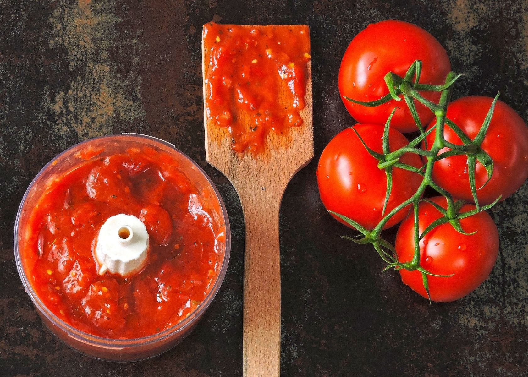 Homemade tomato puree in food processor next to fresh tomatoes and wooden spoon.