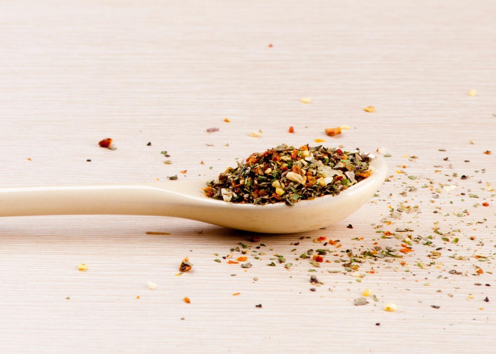 Italian seasoning on wooden spoon. and sprinkled on table.