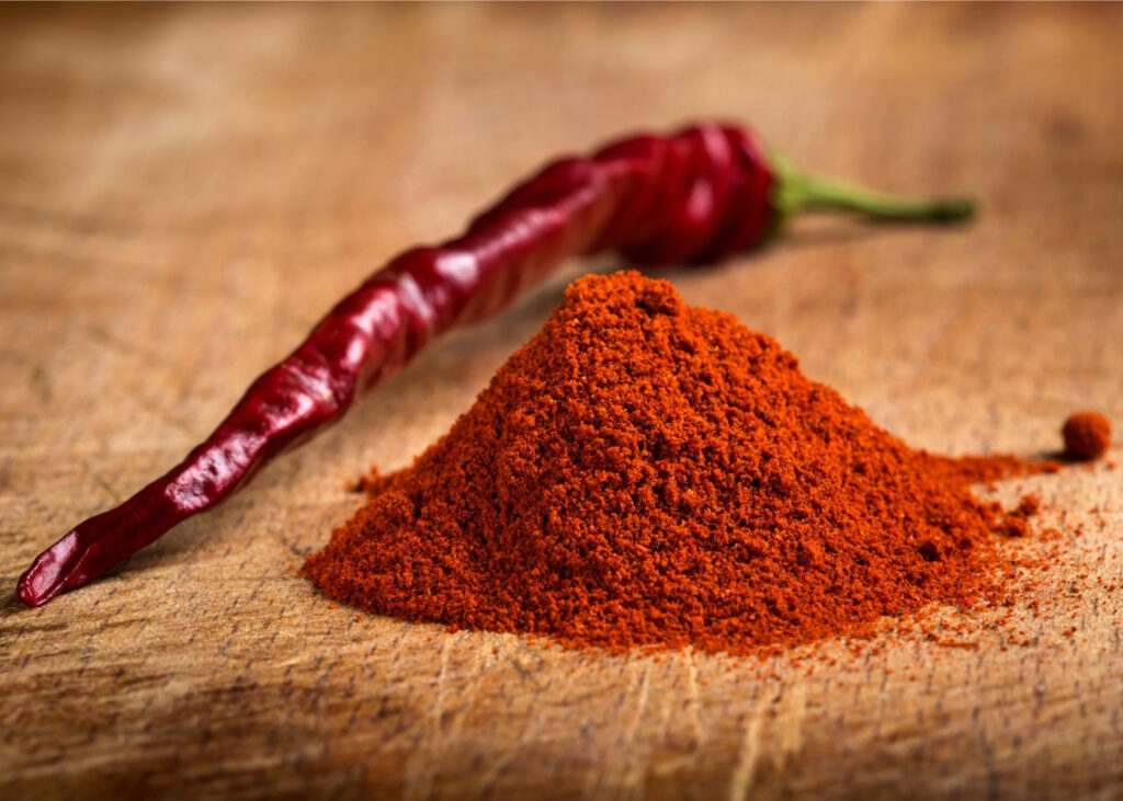 Paprika powder next to red chile.