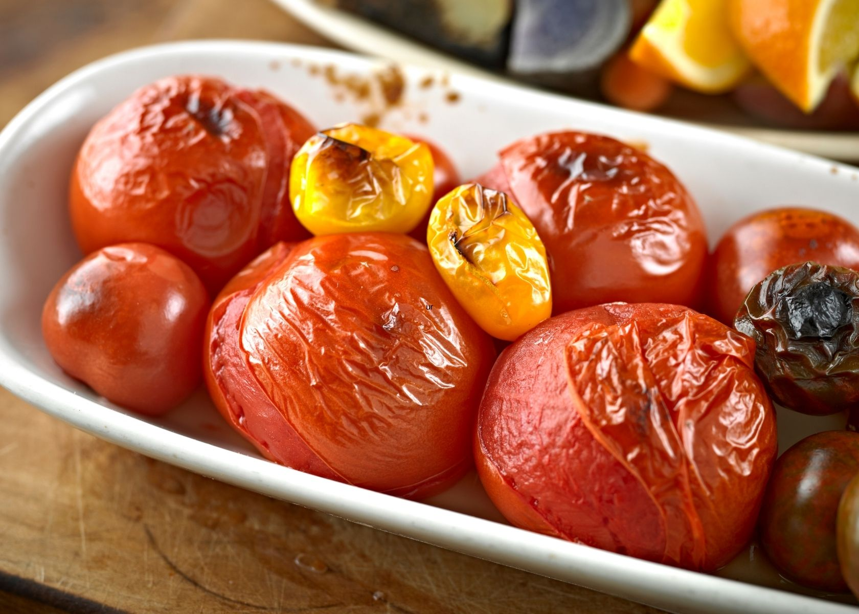 Various size roasted tomatoes in white dish on wood table.