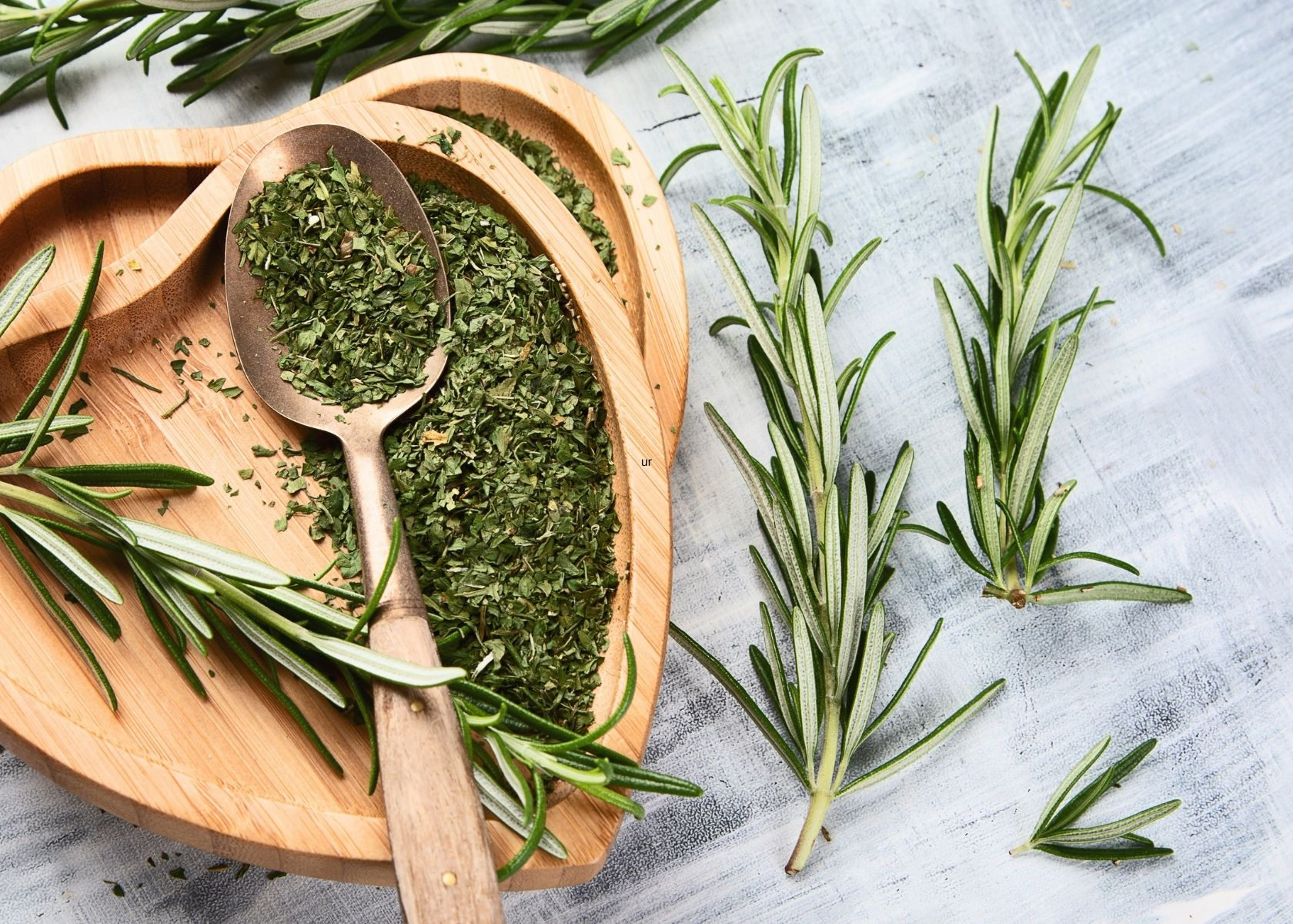 Dried rosemary in heart-shaped wooden bowl next to fresh twigs of rosemary.