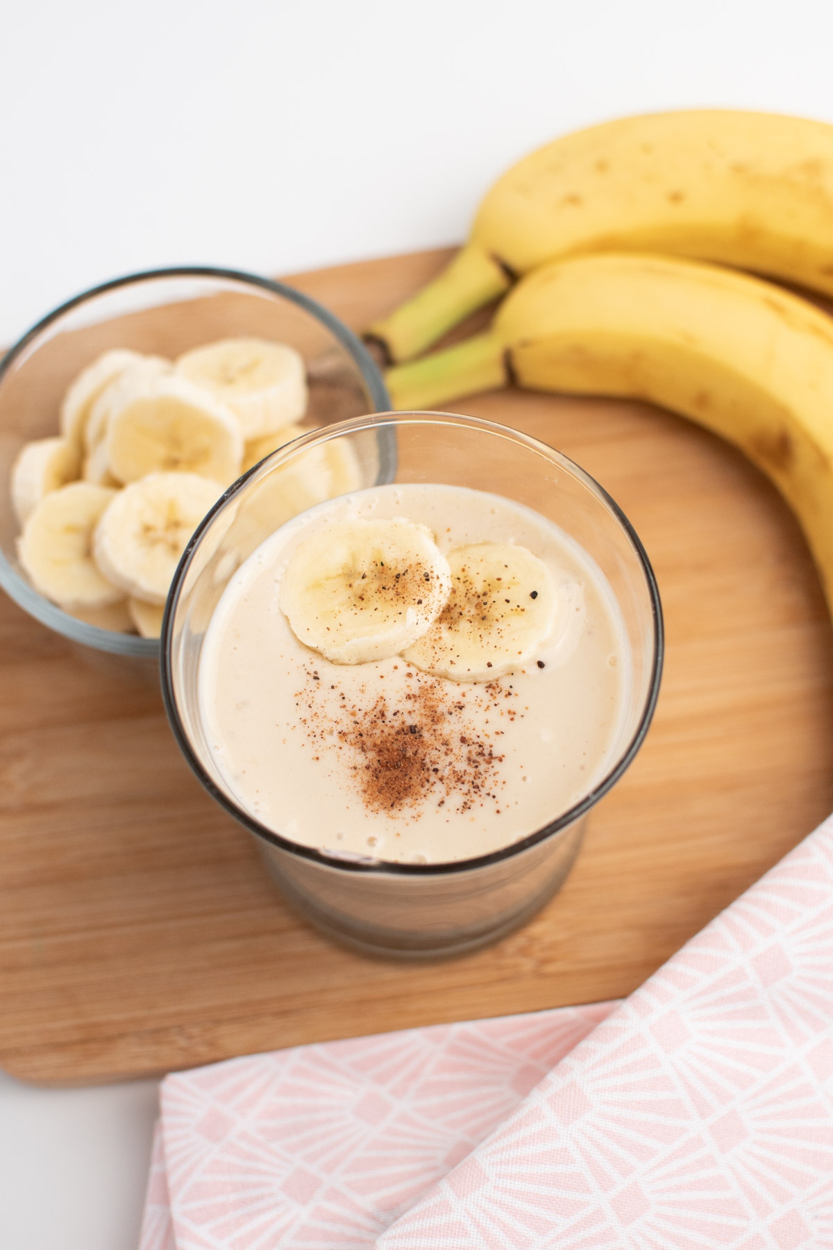 Banana smoothie with nutmeg and sliced bananas in glass next to container of sliced bananas.