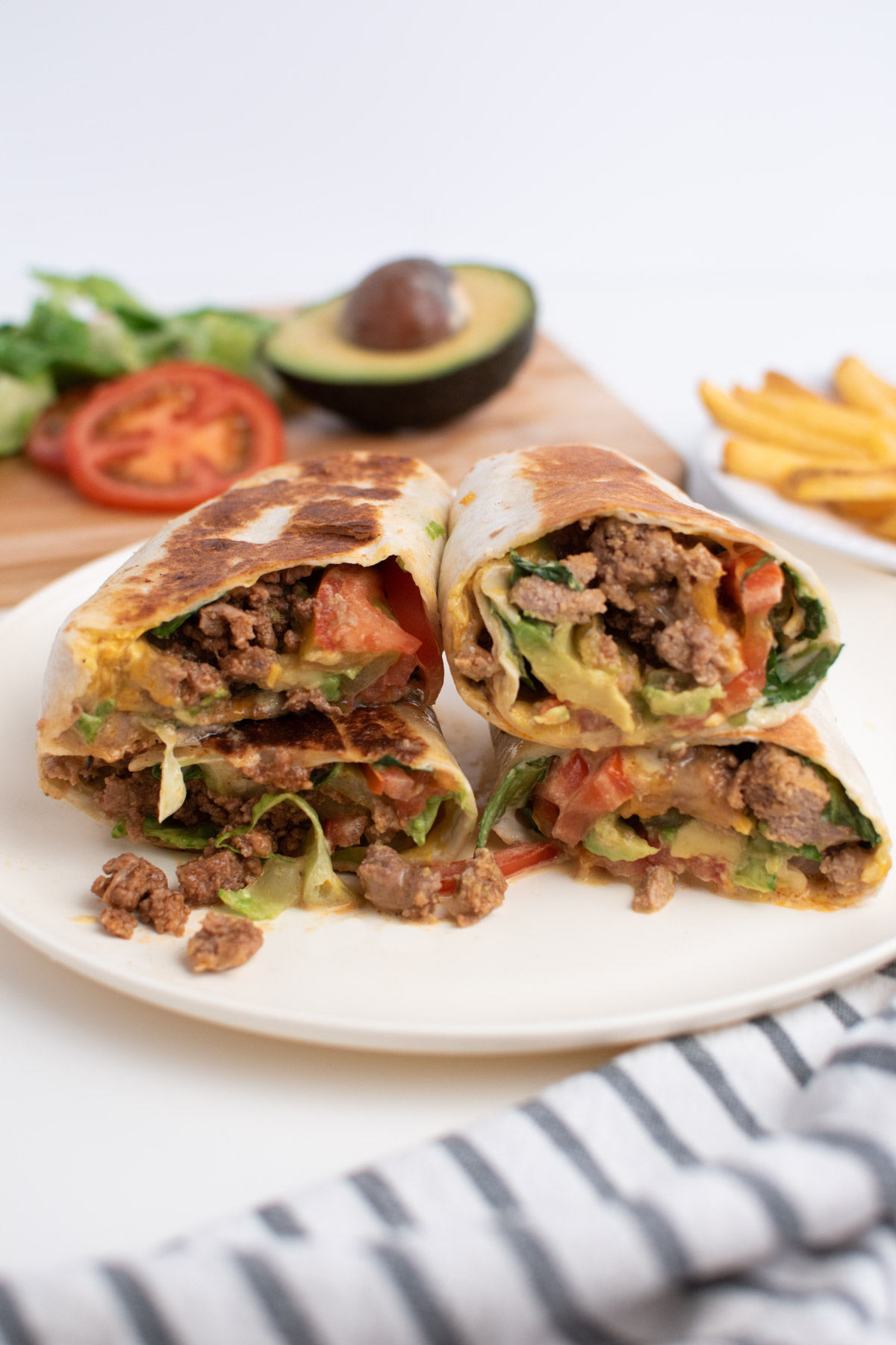 Burger wraps on cream plate next to French fries and burger toppings.