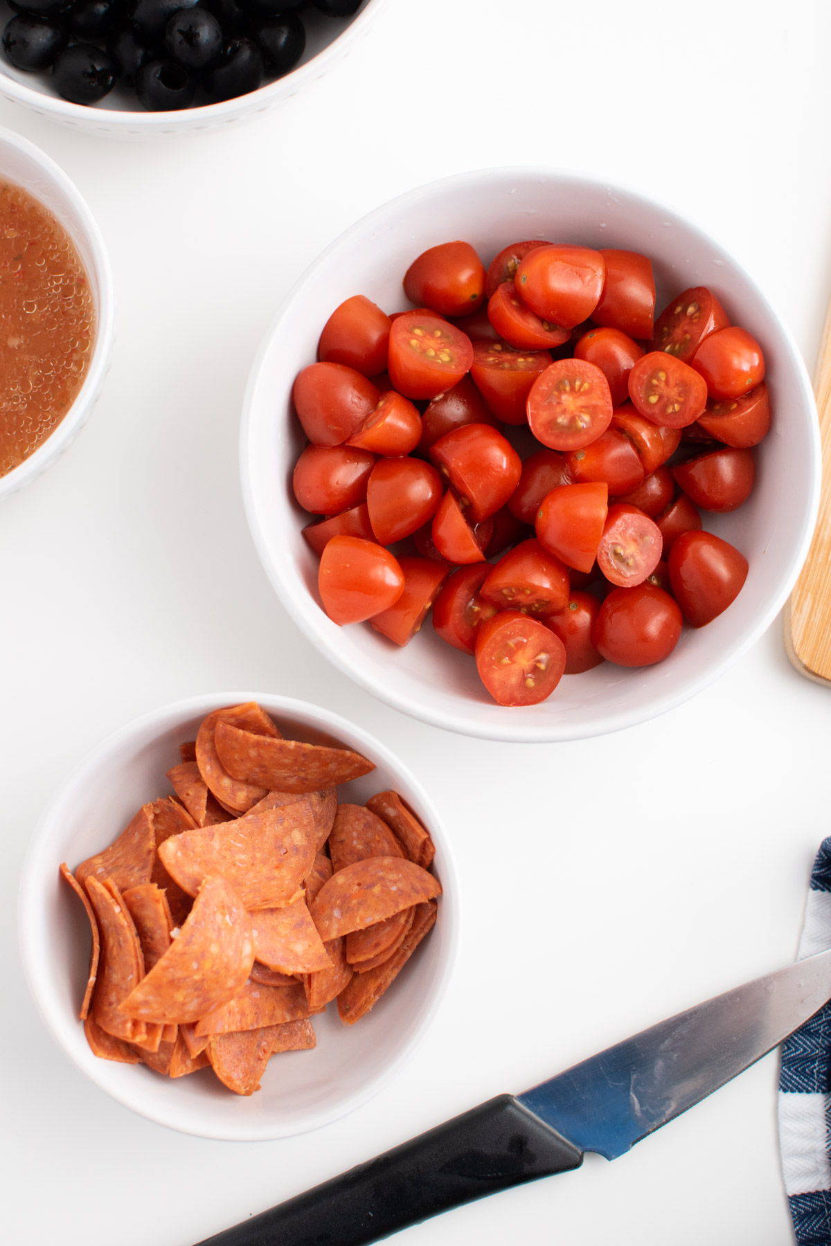 Chopped pepperoni, olives and tomatoes in white kitchen prep bowls on white table.
