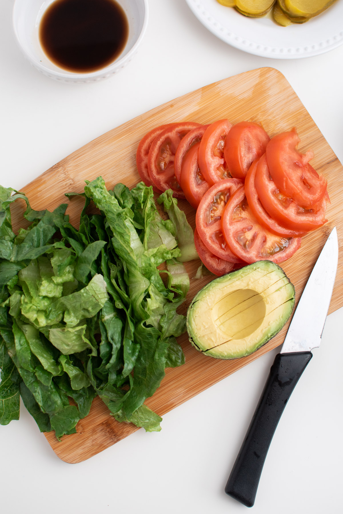 Chopped tomatoes, avocado and lettuce on wooden cutting board with kitchen knife.