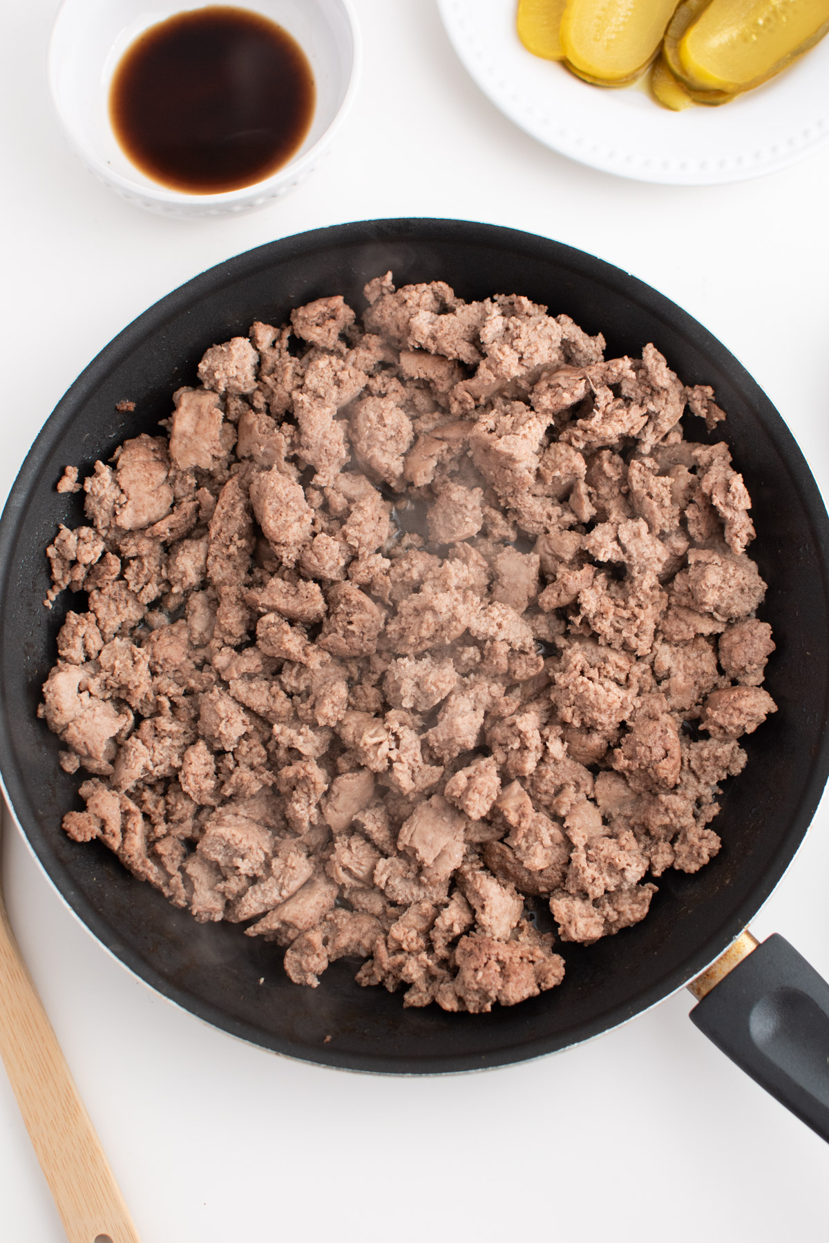 Cooked ground turkey in a black frying pan next to cheeseburger ingredients.