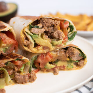 Stack of several grilled cheeseburger wraps on a white plate next to kitchen towel.