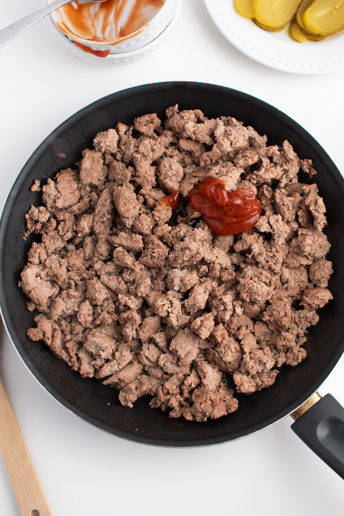 Ketchup and Worcestershire sauce on ground turkey cooked in a black skillet.