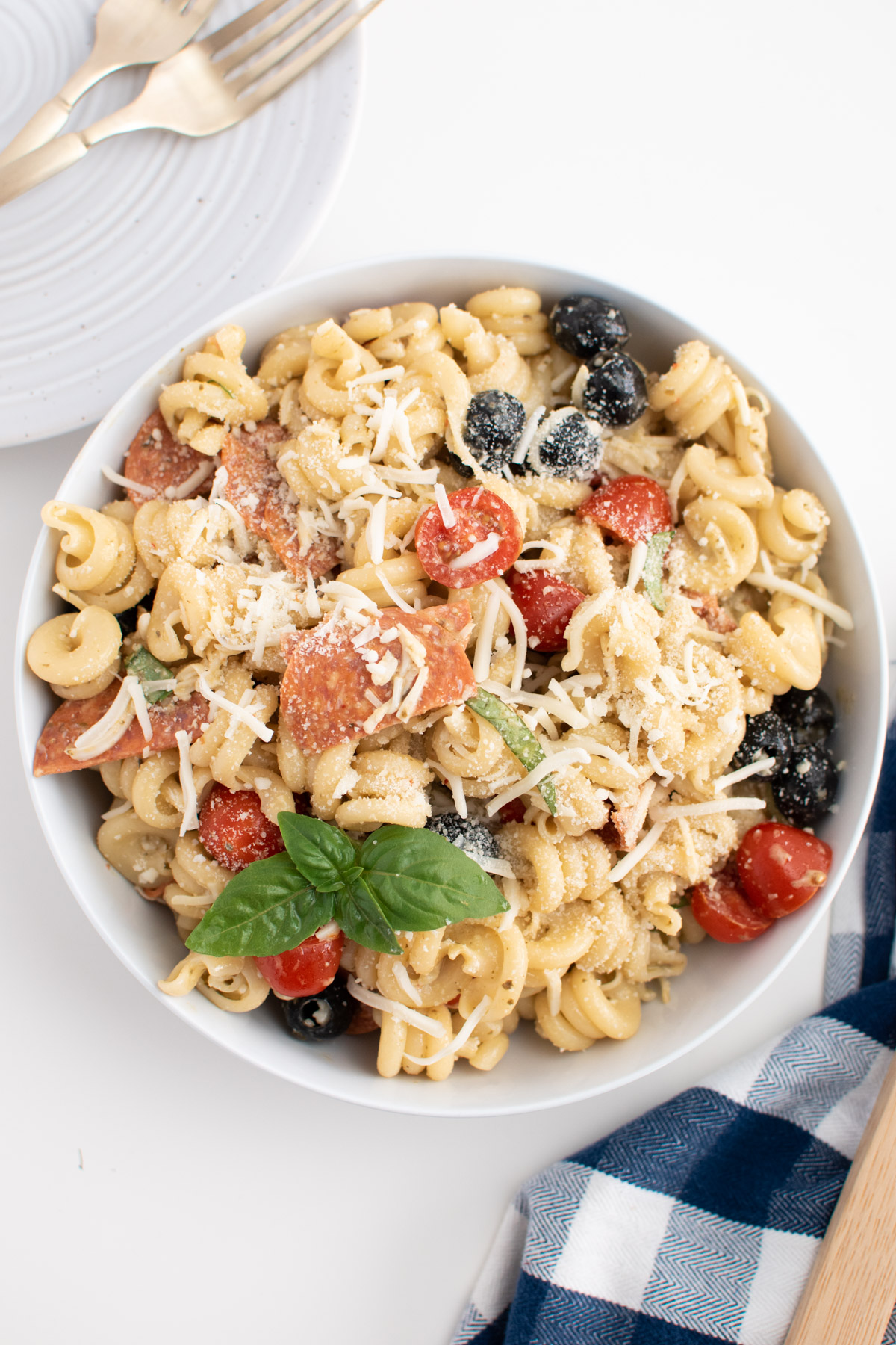 Large white bowl of pizza pasta salad with Parmesan and fresh basil leaves on top.