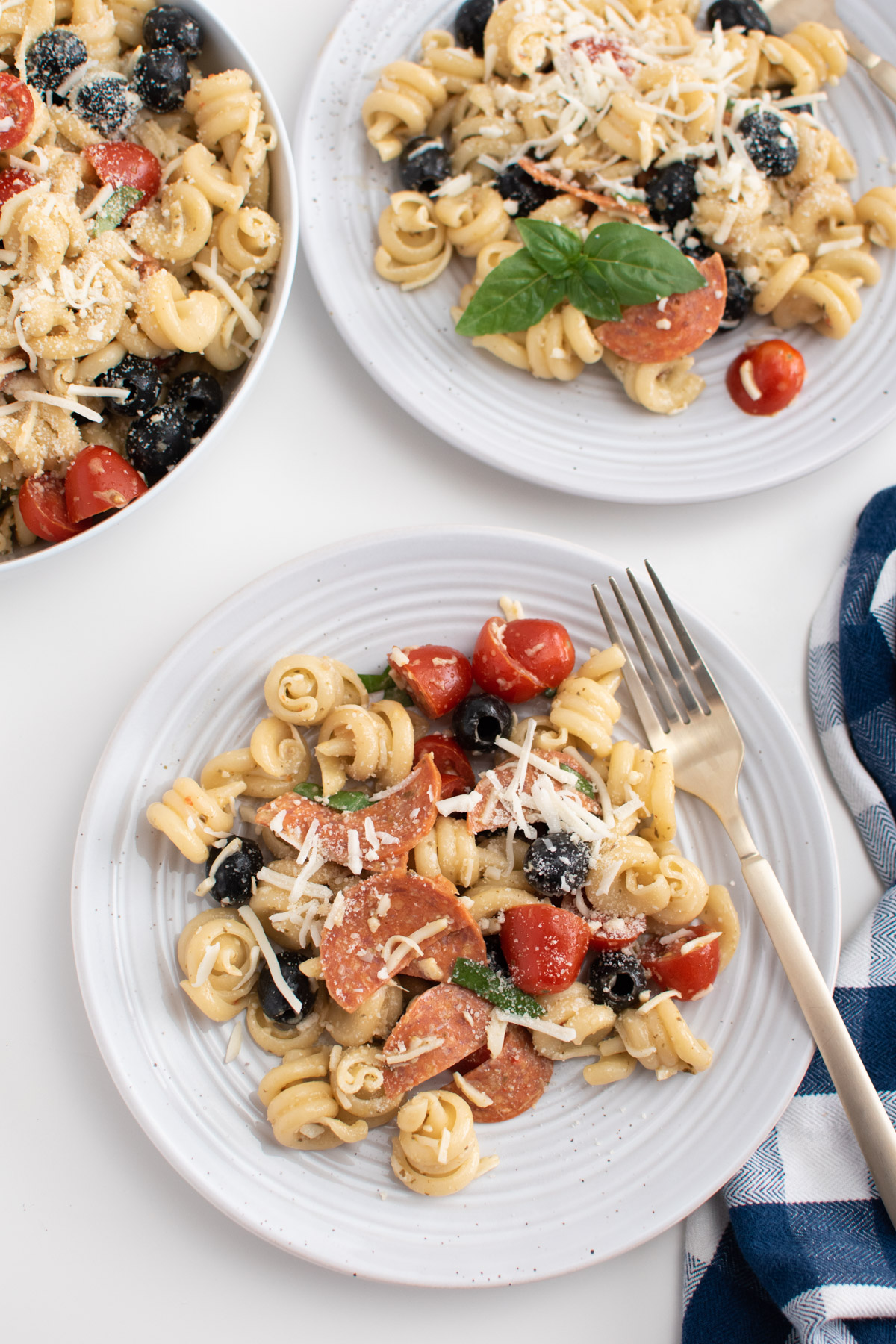 Pepperoni pizza pasta salad on white plates with fork and fresh basil leaves.