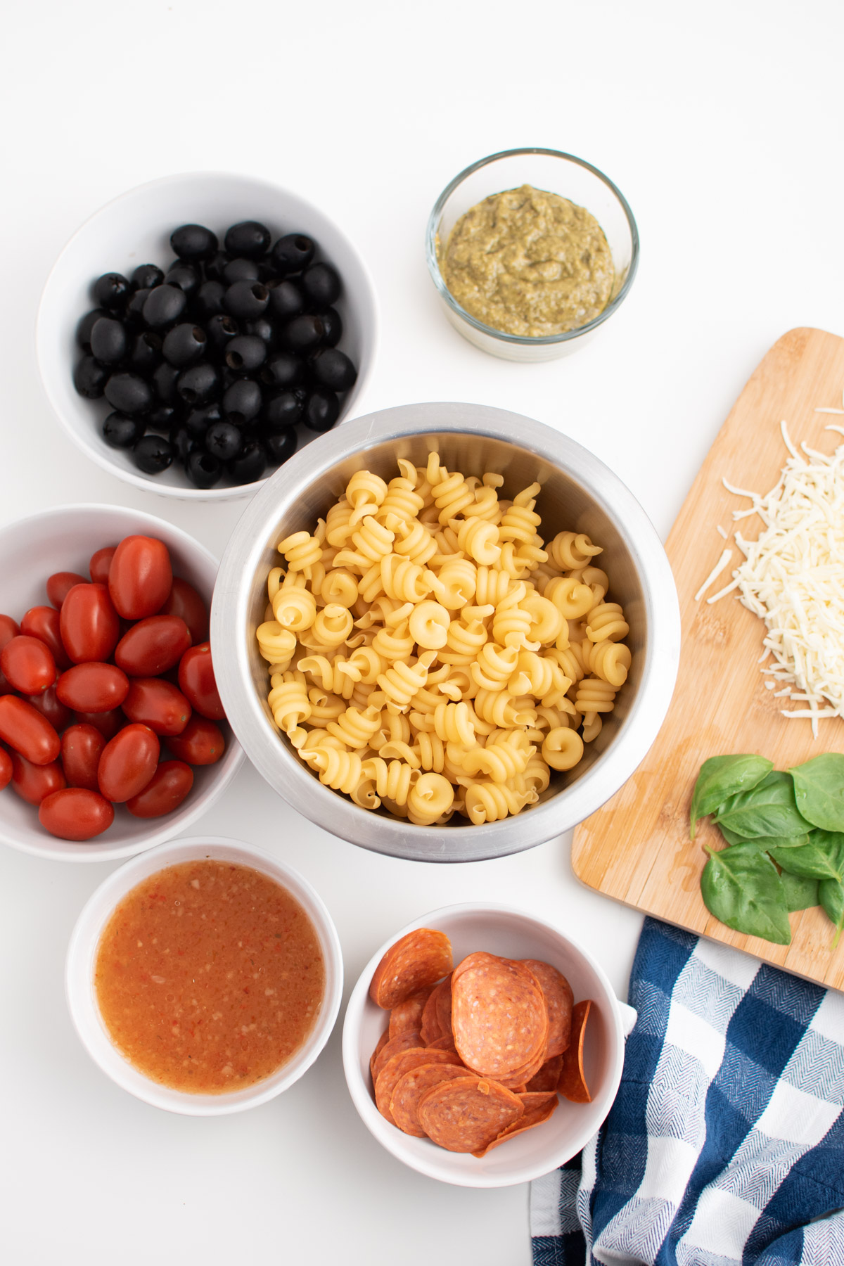 Pizza pasta salad ingredients in white bowls on white table next to cutting board.