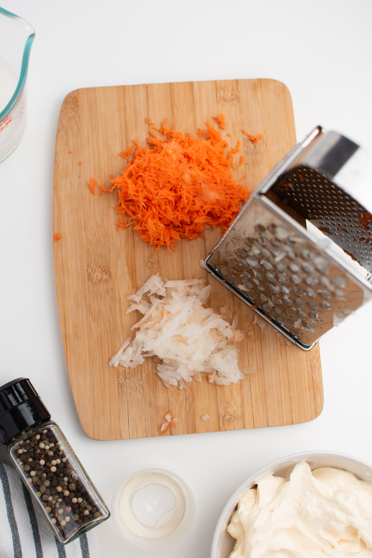Shredded carrots and onion on wood cutting board next to metal grater.