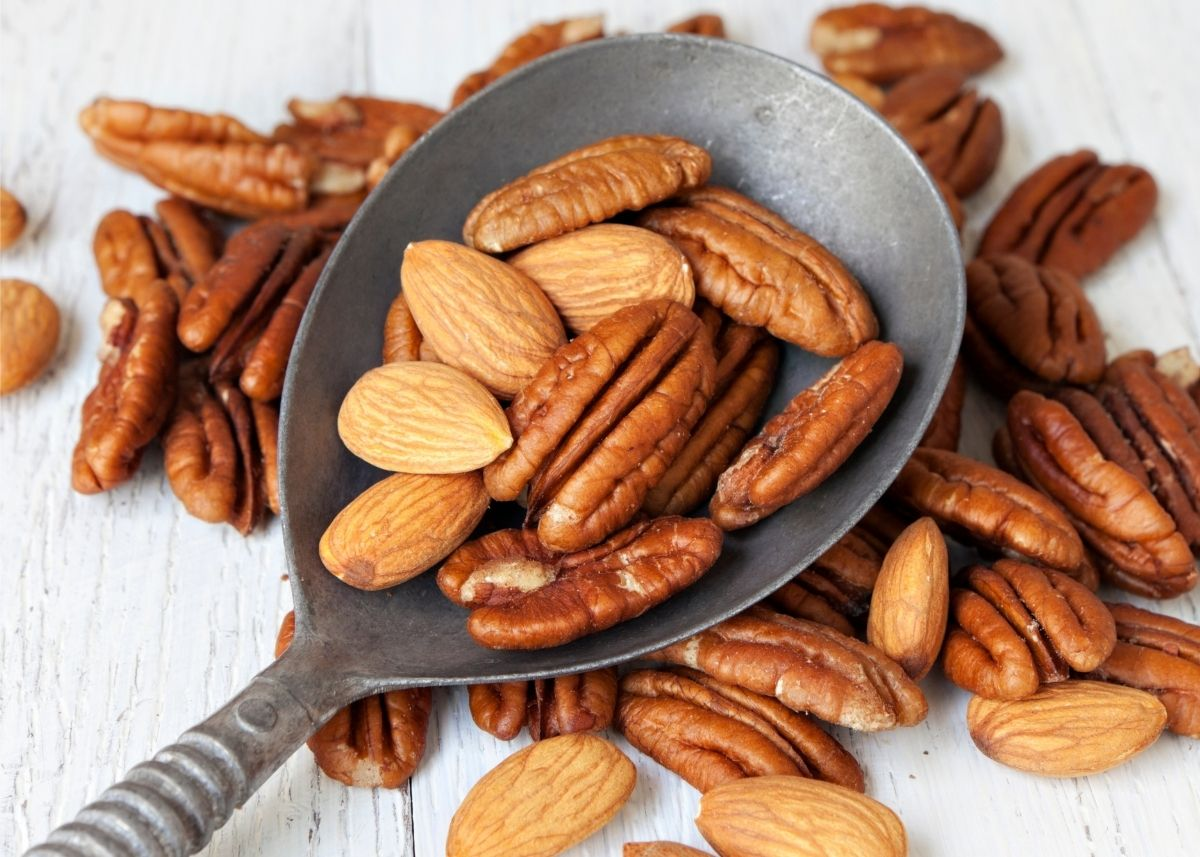 Lots of almonds and pecans spill from a metal spoon onto a table top.