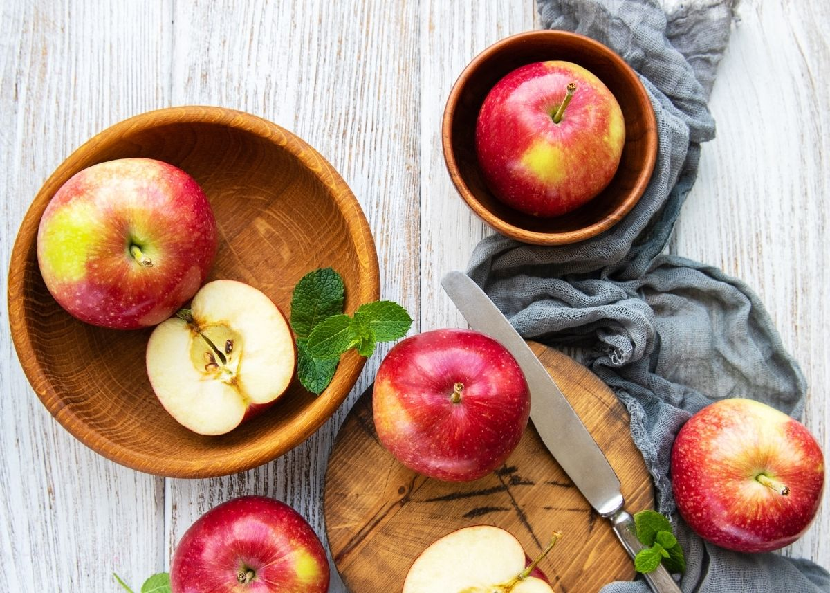 Assortment of whole and cut apples on wooden cutting board and in wooden bowls.