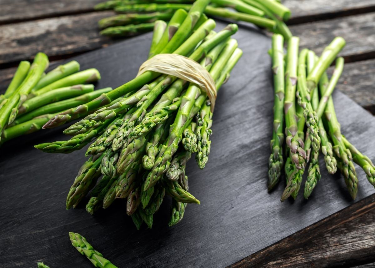 Several bundles of asparagus tied with twine on wooden table and cutting board.