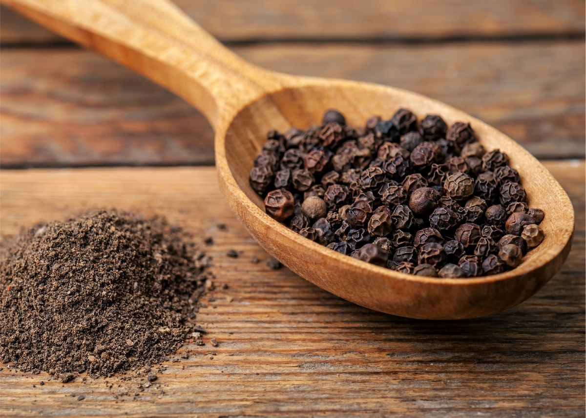 Lots of black peppercorns on a wooden spoon next to pile of ground black pepper.