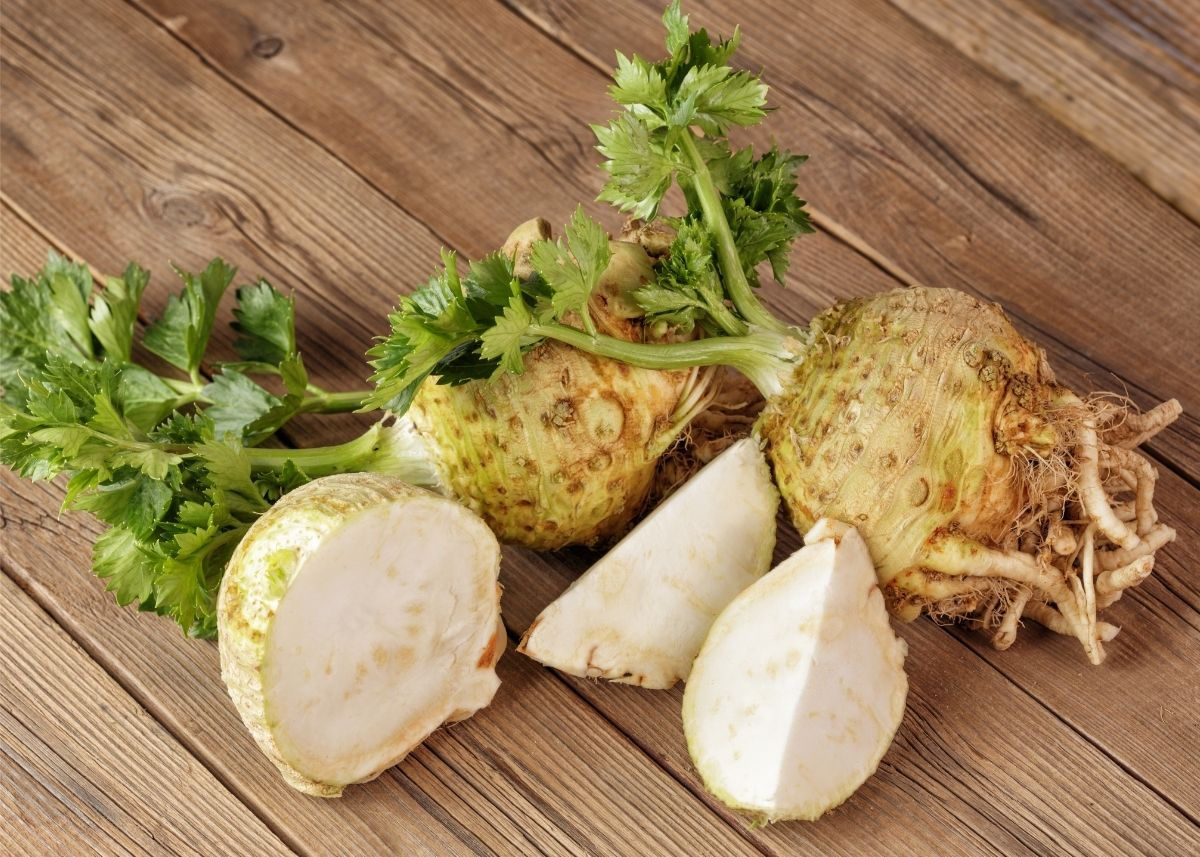 Several celeriac bulbs with green celery shoots on a rustic wooden table.
