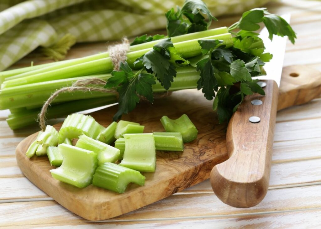 Bundle of celery stalks wrapped in twine next to cut celery on wooden cutting board.