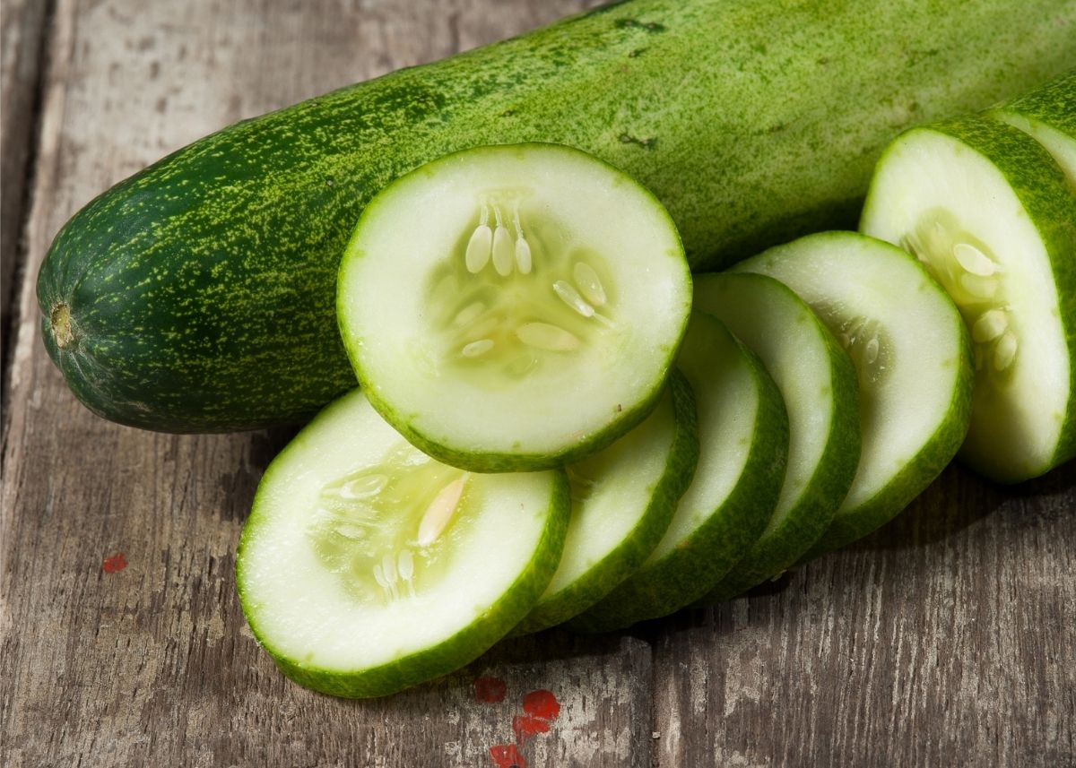 Whole cucumber next to slices of cucumber on a wooden cutting board.