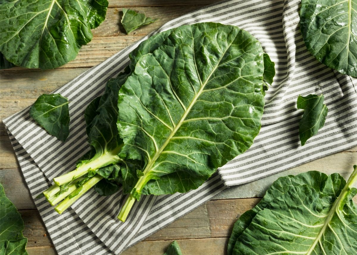 Piles of collard green leaves sitting on a striped kitchen towel on a wooden table.