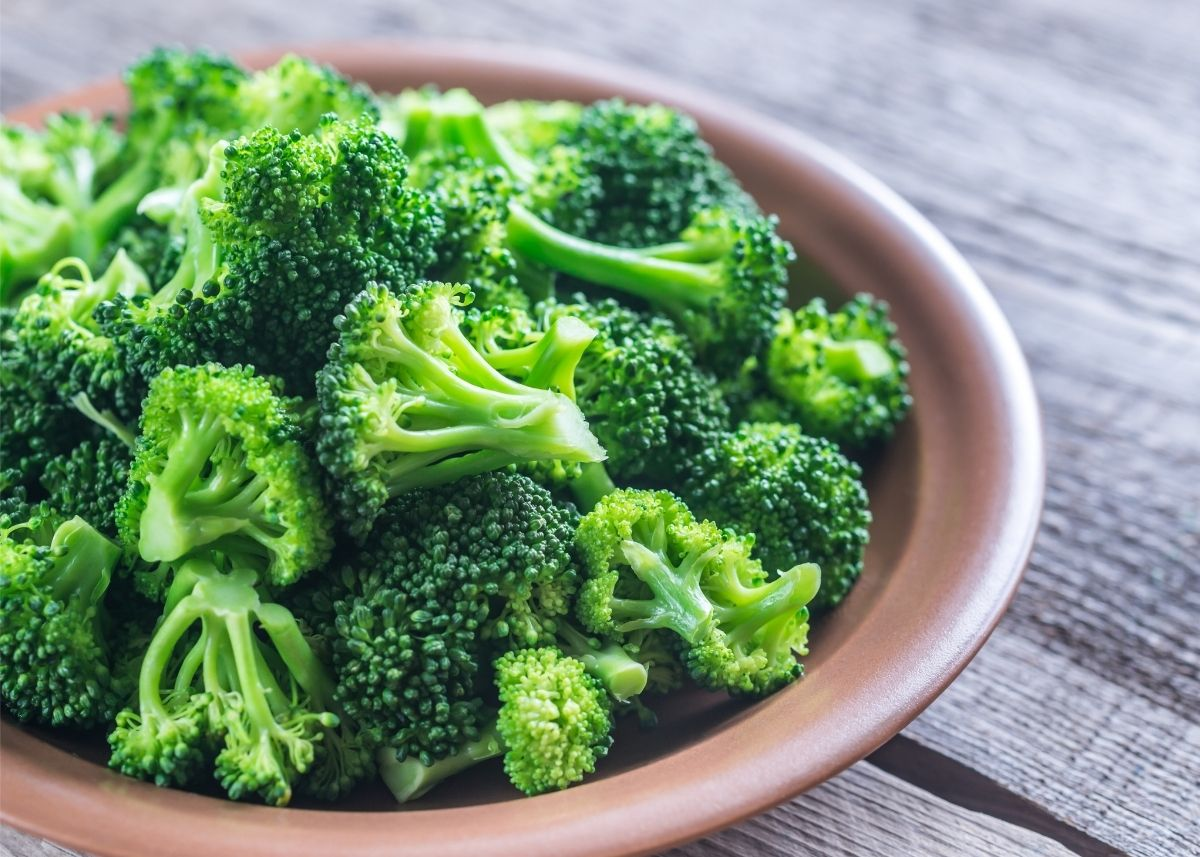 Large brown bowl of bright green cut broccoli on a rustic wooden table.