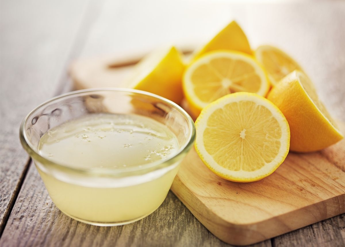 Several cut lemons on a wooden cutting board next to a bowl of lemon juice.