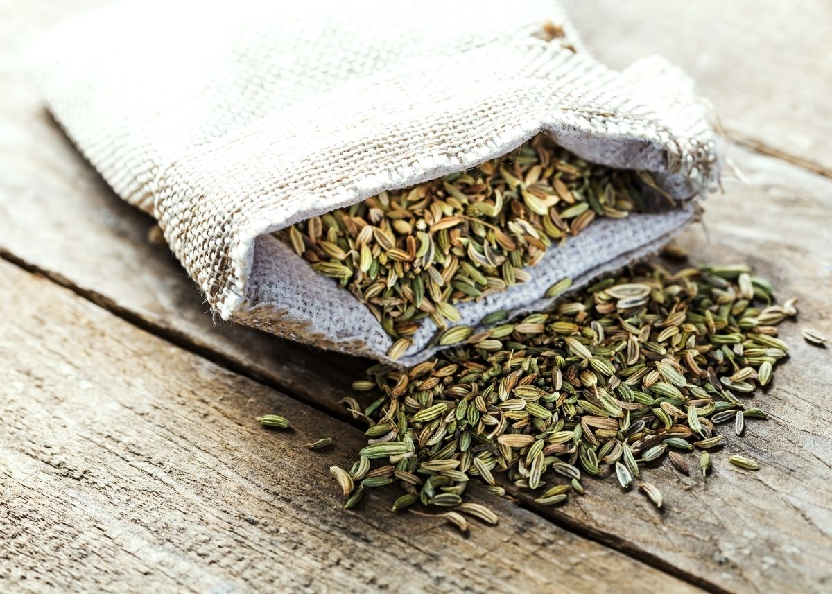 Lots of fennel seeds spilling out of a rustic sack on a wooden table top.