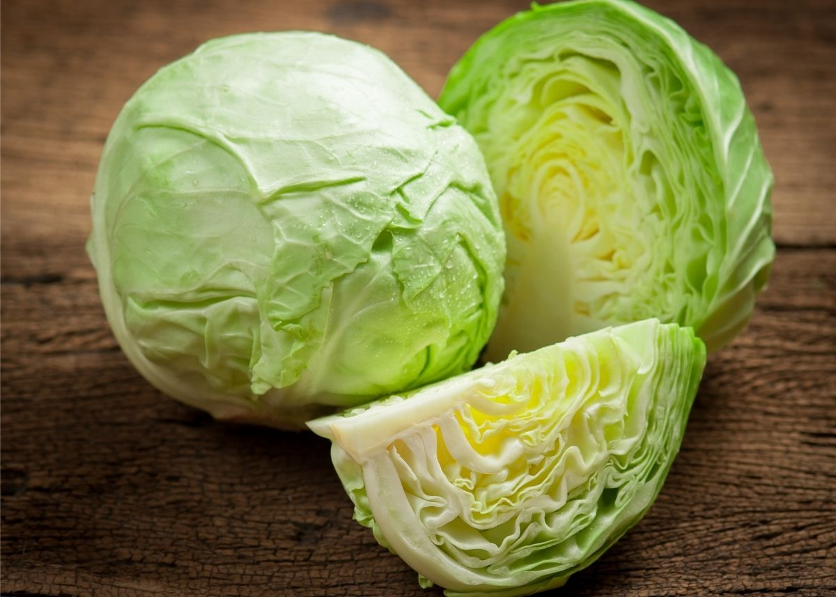 Whole green cabbage next to two green cabbage halves on wooden table.