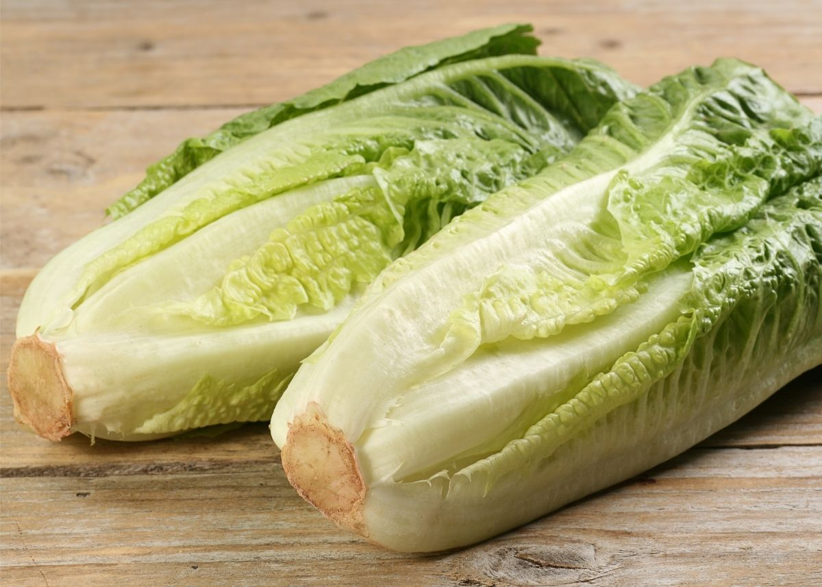 Two hearts of romaine lettuces sitting next to each other on wooden table.