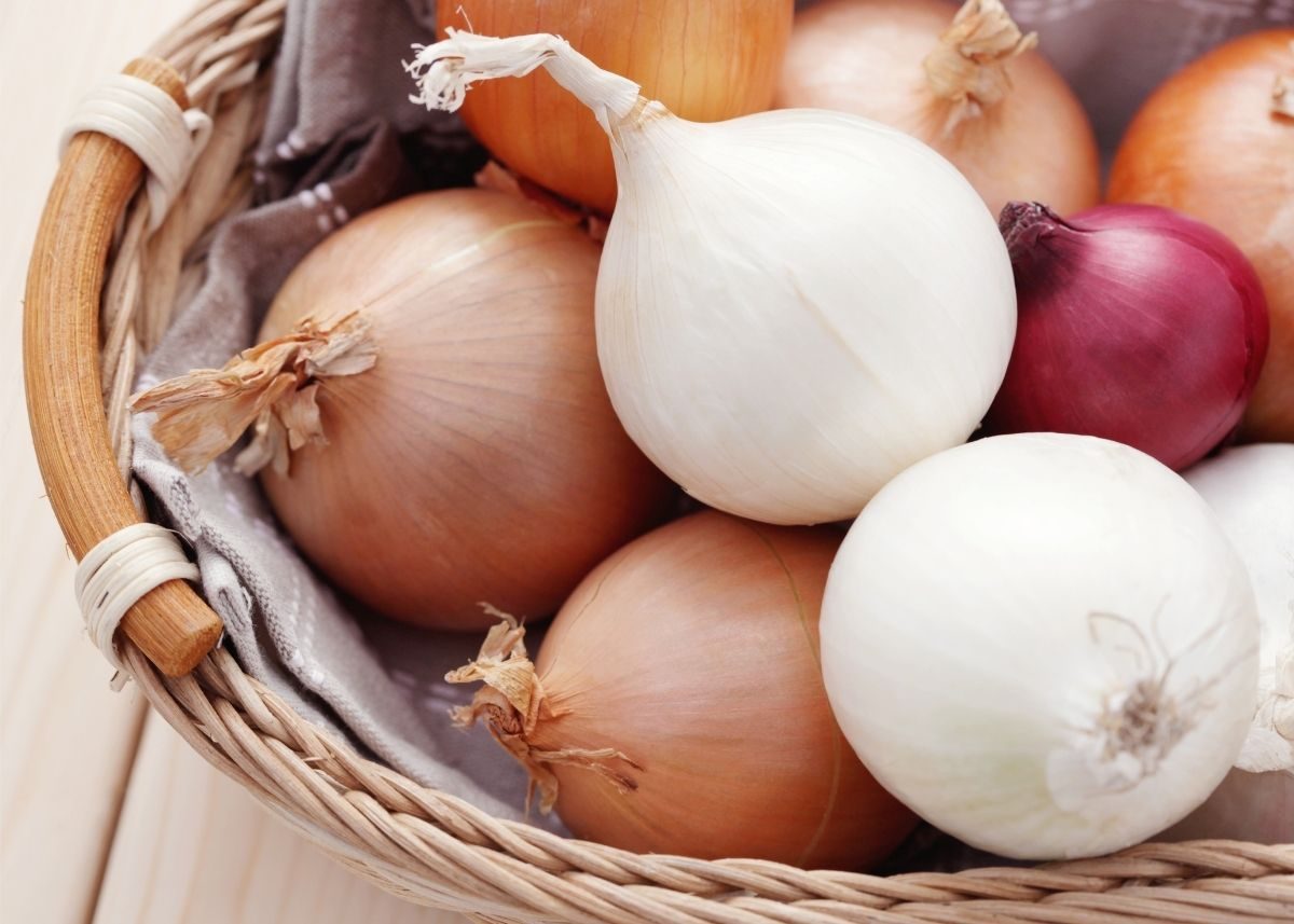 Large rustic wooden basket filled with red, yellow, and white whole onions.